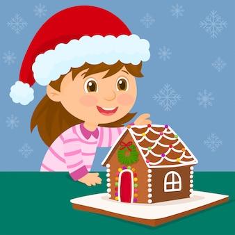Маленькая девочка с колпак санта-клауса и рождественский пряничный домик