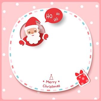 サンタクロースとフレームピンクの背景にプレゼントボックスとメリークリスマス。