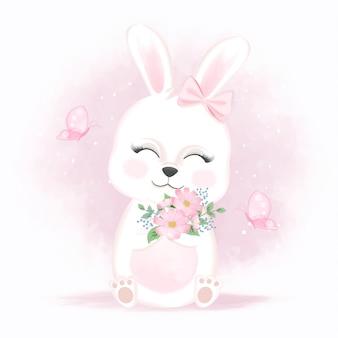 花と蝶を保持しているかわいいウサギ手描き漫画の動物の水彩イラスト