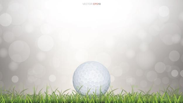緑色の芝生のフィールドと光の白いゴルフボールは、ボケの背景をぼかしました。