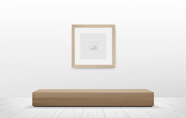 Картинная рамка и деревянная скамья в предпосылке космоса белой комнаты.