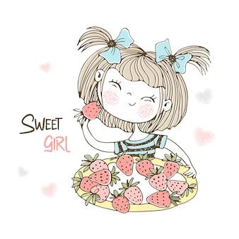 Милая маленькая девочка ест клубнику.