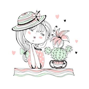 帽子をかぶったかわいい女の子が開花サボテンを賞賛します。