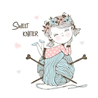 巨大なかせの糸が付いたかわいい小さな編み物。