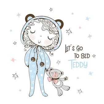 おもちゃのテディベアと一緒に寝るクマの形のパジャマ姿のかわいい女の子。