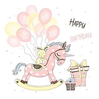 ユニコーンのおもちゃの馬と風船とギフトを持つ少女の誕生日カード。