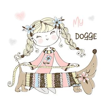 かわいい裁縫師の女の子が彼女のダックスフント犬のセーターを編んでいました。