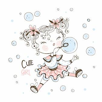Милая маленькая девочка дует мыльные пузыри.