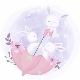 Детские зайчики играют с зонтиком