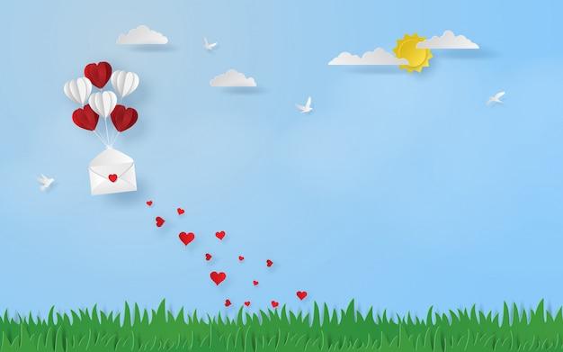 空に浮かんだ開いた手紙を持つ心臓の形をした風船