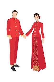 手を繋いでいる伝統的な赤いドレスの中国の結婚式のカップル
