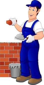 男の建物のレンガの壁。制服を着た建設労働者