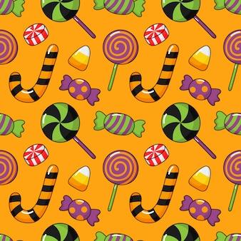 幸せなハロウィーンのシームレスパターンとオレンジ色で分離された漫画キャンディー