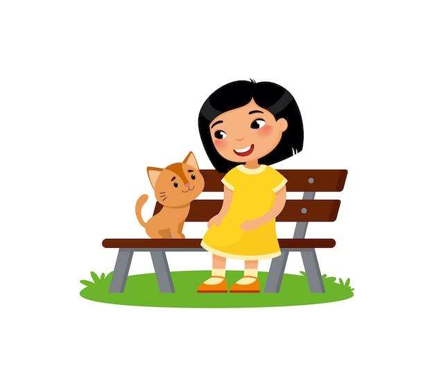 かわいい小さなアジアの女の子とキティがベンチに座っています。幸せな学校や未就学児と彼女のペットが一緒に遊んでいます。