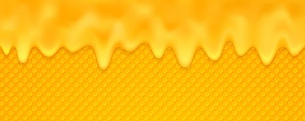 オレンジの蜂蜜の背景がハニカムで溶けています。