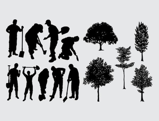 掘る労働者と木のシルエット