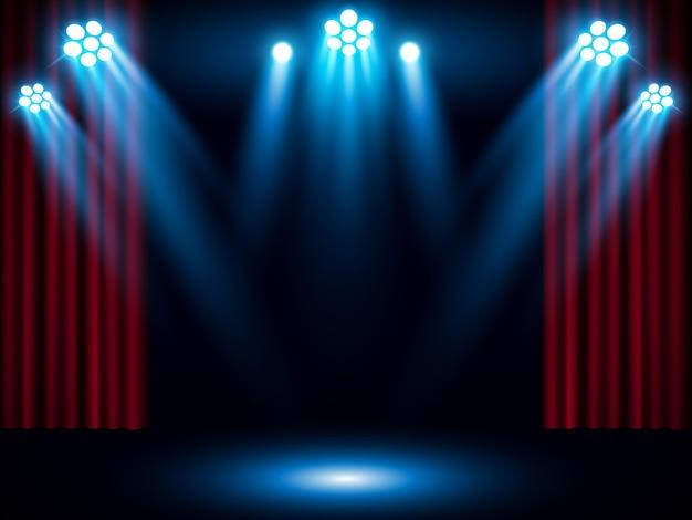 青いスポットライト付きの赤いステージのカーテン