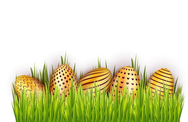 Украшенные золотые пасхальные яйца в свежей зеленой траве на белом фоне