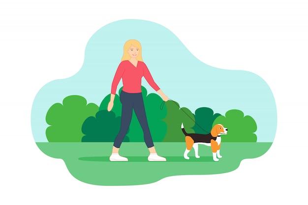 彼女の小さなビーグル犬と一緒に公園を散歩
