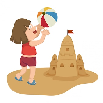 小さな女の子がボールとビーチで遊んで