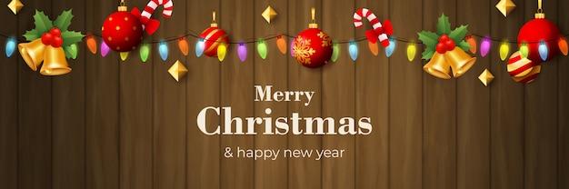 茶色の木製の地面にガーランドとメリークリスマスバナー