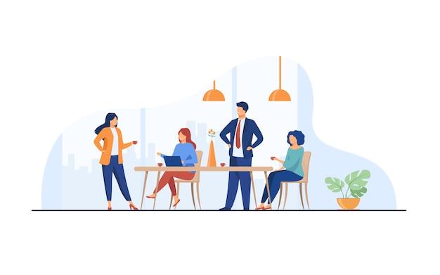従業員がオフィスキッチンで会議を行い、コーヒーを飲む