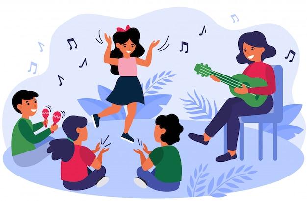 Счастливые дети веселятся во время урока музыки