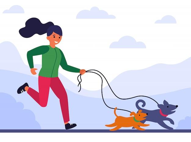 Молодая женщина бегает и гуляет с собаками