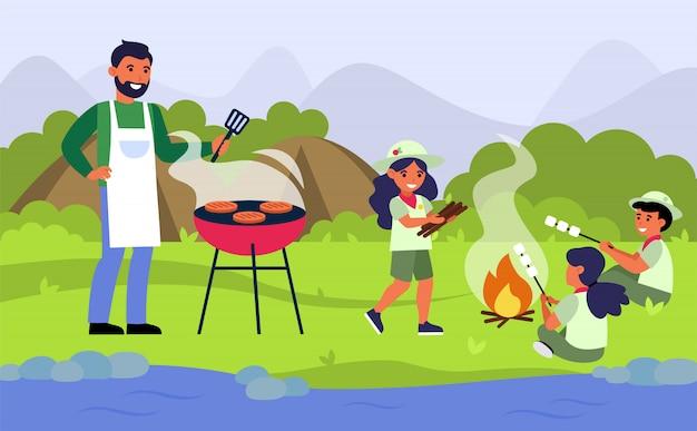川の土手でバーベキューピクニックを持っている家族