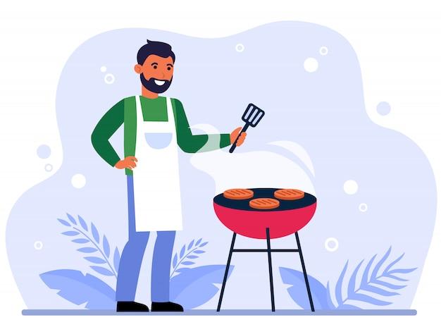 幸せな男のバーベキュー肉を焼く