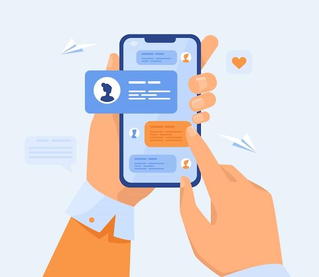 Человеческая рука держит мобильный телефон с текстовыми сообщениями