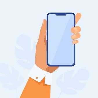 Человеческая рука держит мобильный телефон