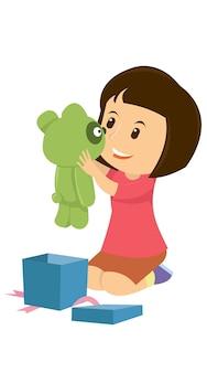 テディベアの贈り物を開いている幸せな女の子