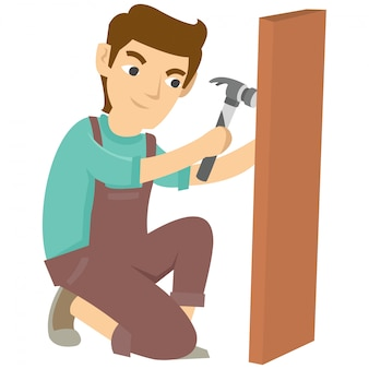 大工は木の何かを作るためにハンマーと釘を使う