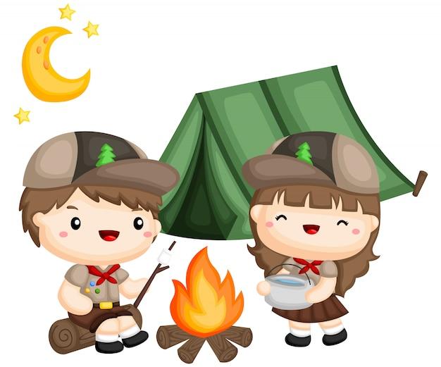 Мальчик и девочка-скауты готовят еду возле палатки