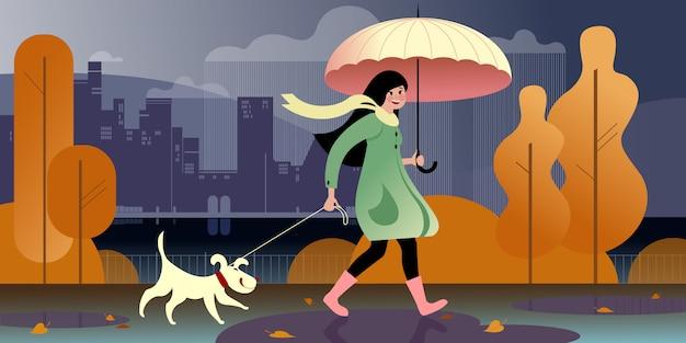 傘の下の少女は、堤防沿いの秋の公園で犬と一緒に歩きます。都市通りのシーン。