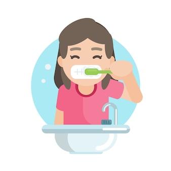 幸せなかわいい女の子の浴室で歯を磨く