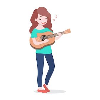 Счастливая молодая девушка играет на гитаре и поет песню.