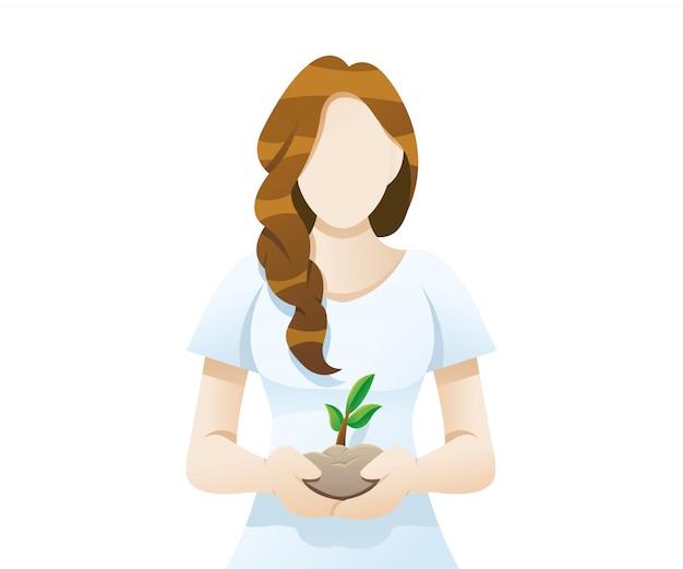 Молодая женщина держит почву и цветок в руке