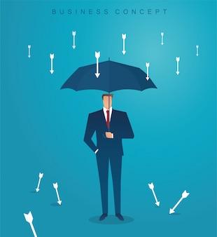 ビジネスマンが下向きの矢印を保護するために傘を使用する