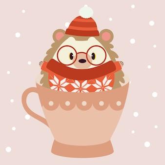 かわいいハリネズミのキャラクターは赤い冬の帽子と大きなメガネと赤いセーターを着て、大きなピンクのカップに座っています