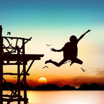 Силуэт и прыжки мальчик в сумерках с голубым небом.