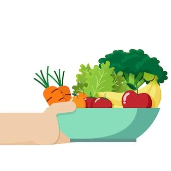 ボウルを持っている手は新鮮な野菜や果物でいっぱいになります