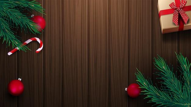 Подарок, конфета, ветви елки, елочные шары на деревянный стол. фон