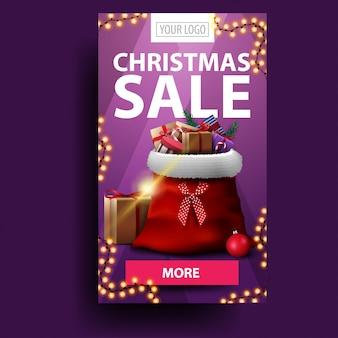 クリスマスセール、ボタンと垂直のモダンな割引バナー、ロゴとプレゼントとサンタクロースのバッグのための場所