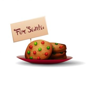 分離されたプレートに赤と緑のキャンディーとサンタクロースのクッキー