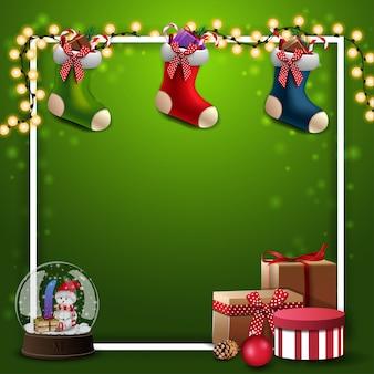 Зеленый квадратный фон с гирляндой, белая рамка, подарки, снежный шар, рождественские чулки