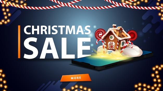 Новогодняя распродажа, синий дисконтный баннер для сайта с гирляндами, кнопкой и смартфоном, на экране которого появляются рождественские пряничные домики
