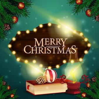 木製のサインとクリスマスの本を持つクリスマスカード