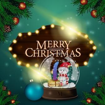 木製のサインとスノーグローブのクリスマスカード